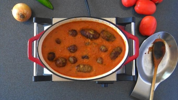 Broiled koftas added to seasoned tomato based gravy.