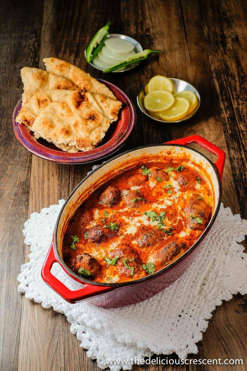 Kebab Kofta Masala is a delicious Indian dish of succulent grilled or broiled meatballs in a rich, creamy and spicy gravy. Served here with some naan and lemon slices.
