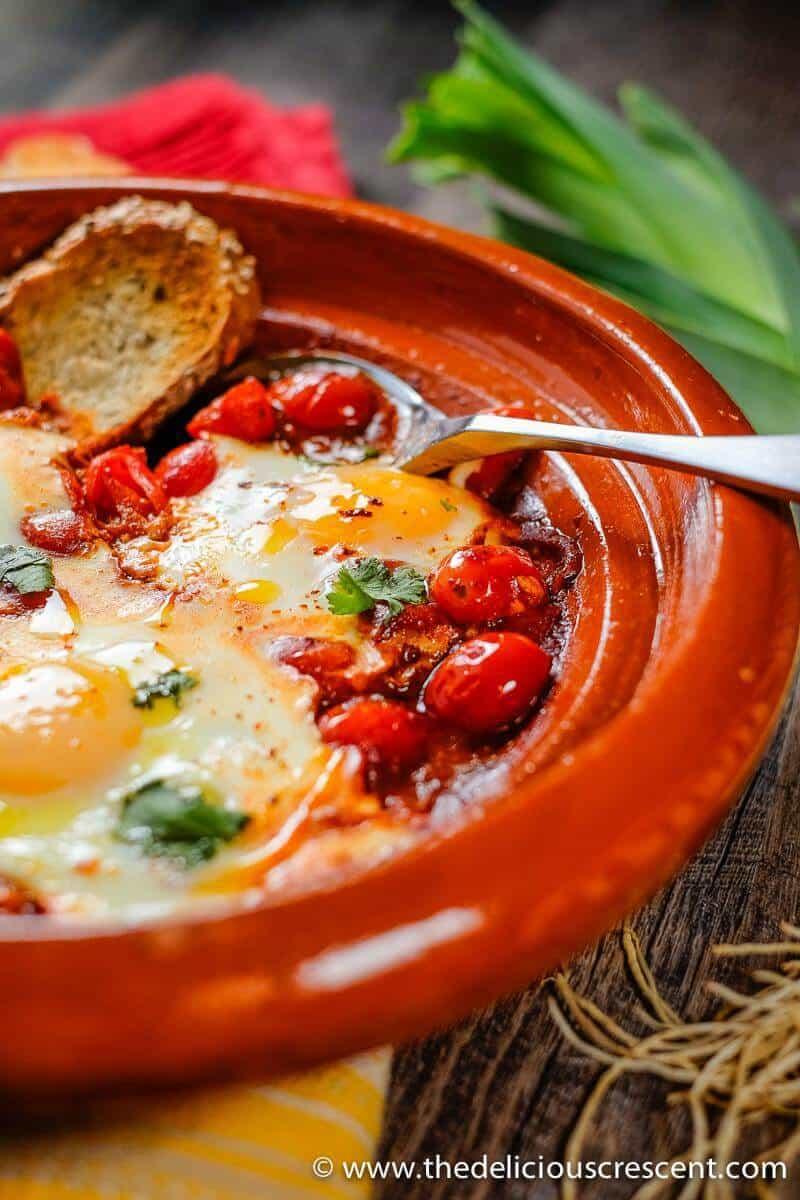 Moroccan Eggs in Tomato Sauce with a piece of bread and a spoon.