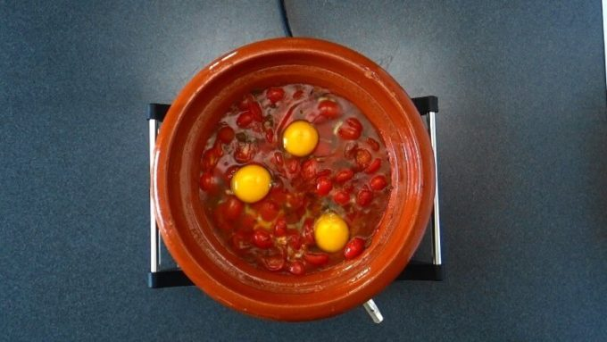 Moroccan Eggs in Tomato Sauce. Eggs are cracked and added to the tomato sauce.