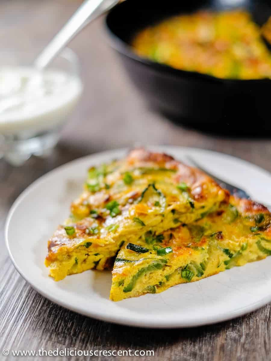 Slices of baked zucchini omelette on a a white plate served with a dip.