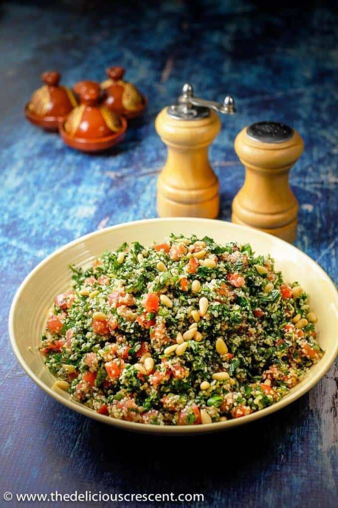 Tabbouleh salad served in a cream bowl and placed on a table.