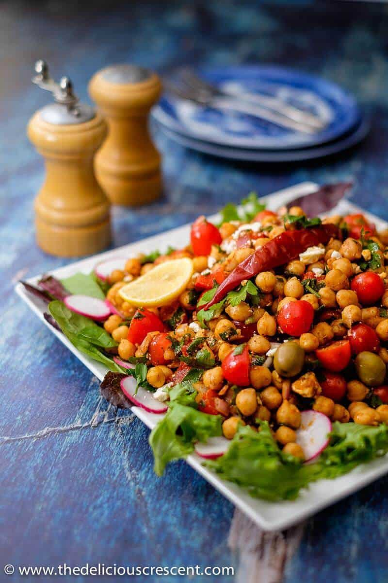 A side view of the chickpea salad on a white serving plate.