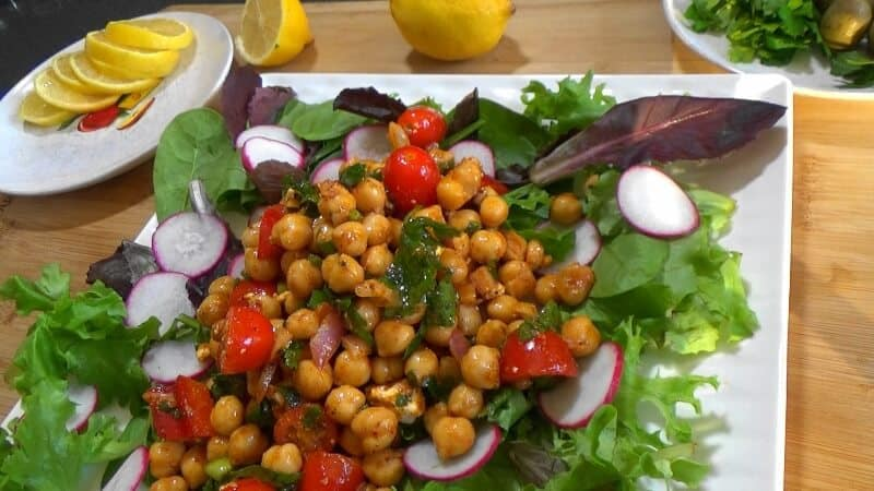 Mediterranean Chickpea Salad placed over a bed of salad leaves and sliced radish.