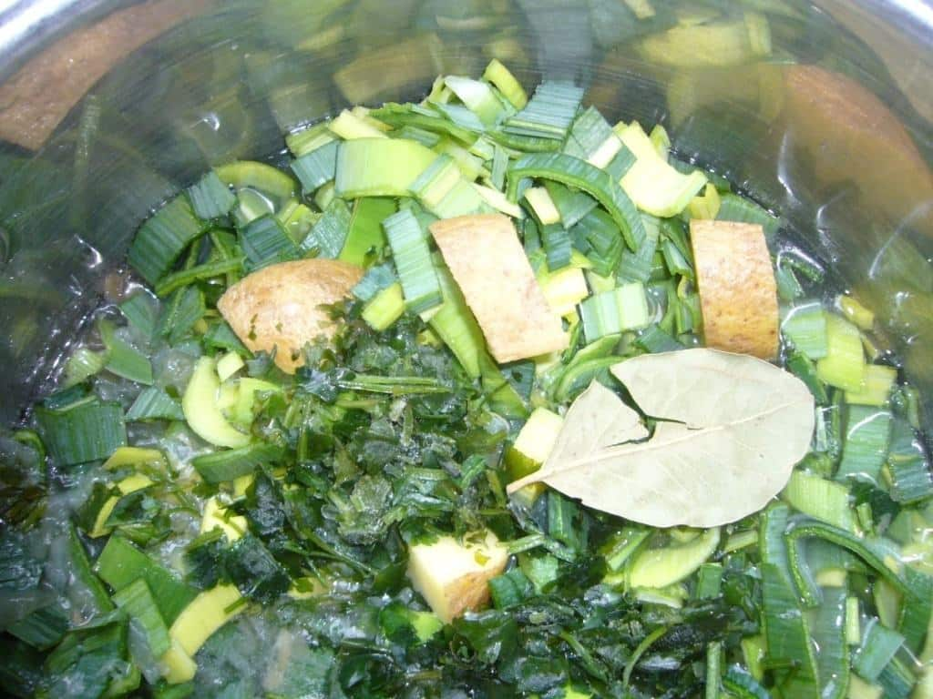 The ingredients of creamy leek avocado soup in the cooking pot.