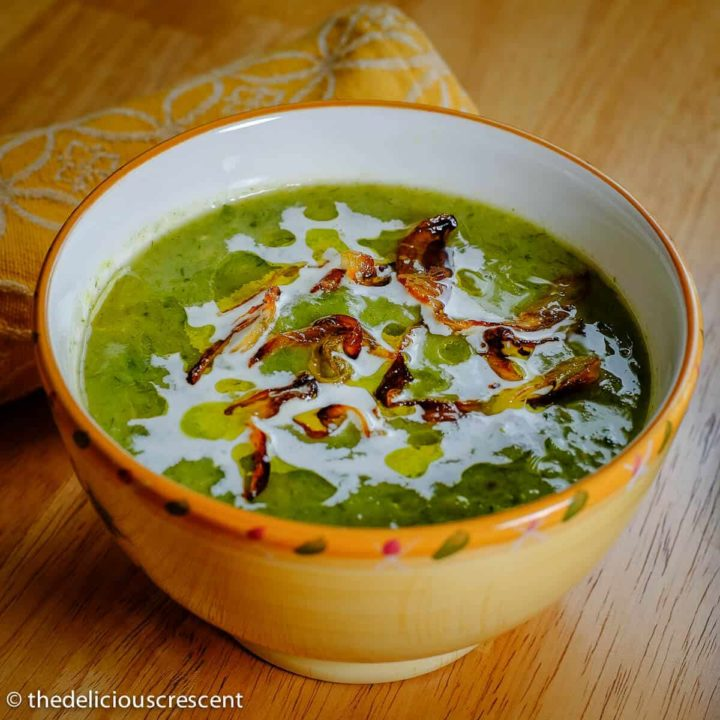 A bowl of creamy leeks avocado soup placed on the table.