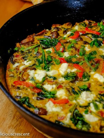 Mushroom frittata with spinach, red pepper and cheese baked in a cast iron skillet.