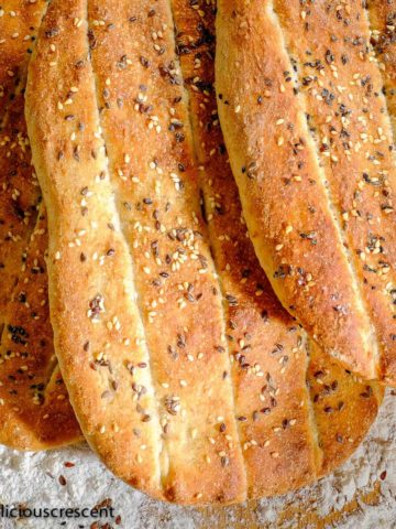 Several Persian barbari bread loaves placed on a table with flour dusted around.