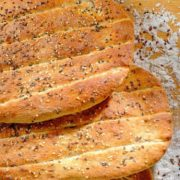A stack of Persian barbari bread on a table dusted with flour.