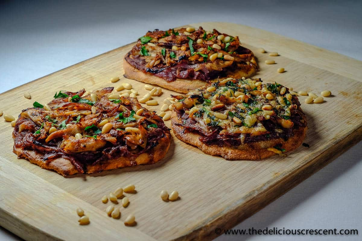 Three sumac chicken caramelized onion flatbread (Musakhan) with pine nuts on a wooden board