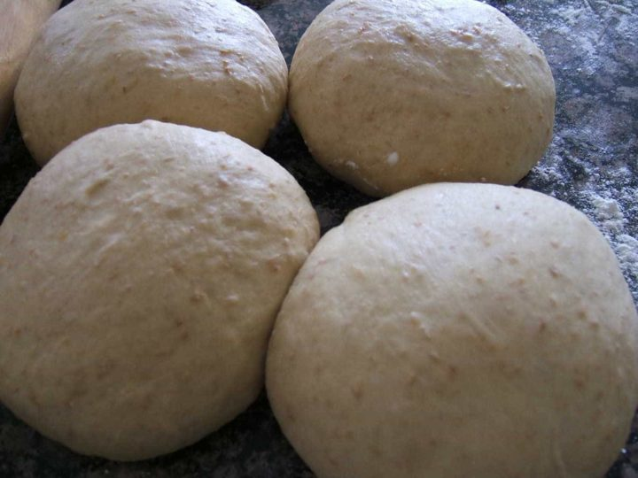 Yeast based dough balls placed on a counter.