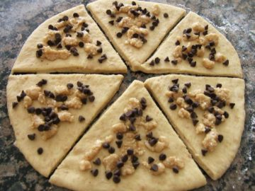 Rolled out dough cut into triangles and topped with chocolate and hazelnuts.