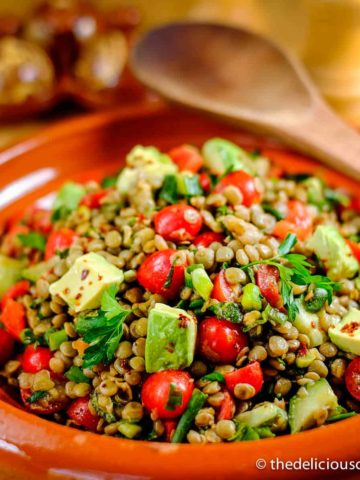 Spicy lentil salad with avocado in a serving dish.