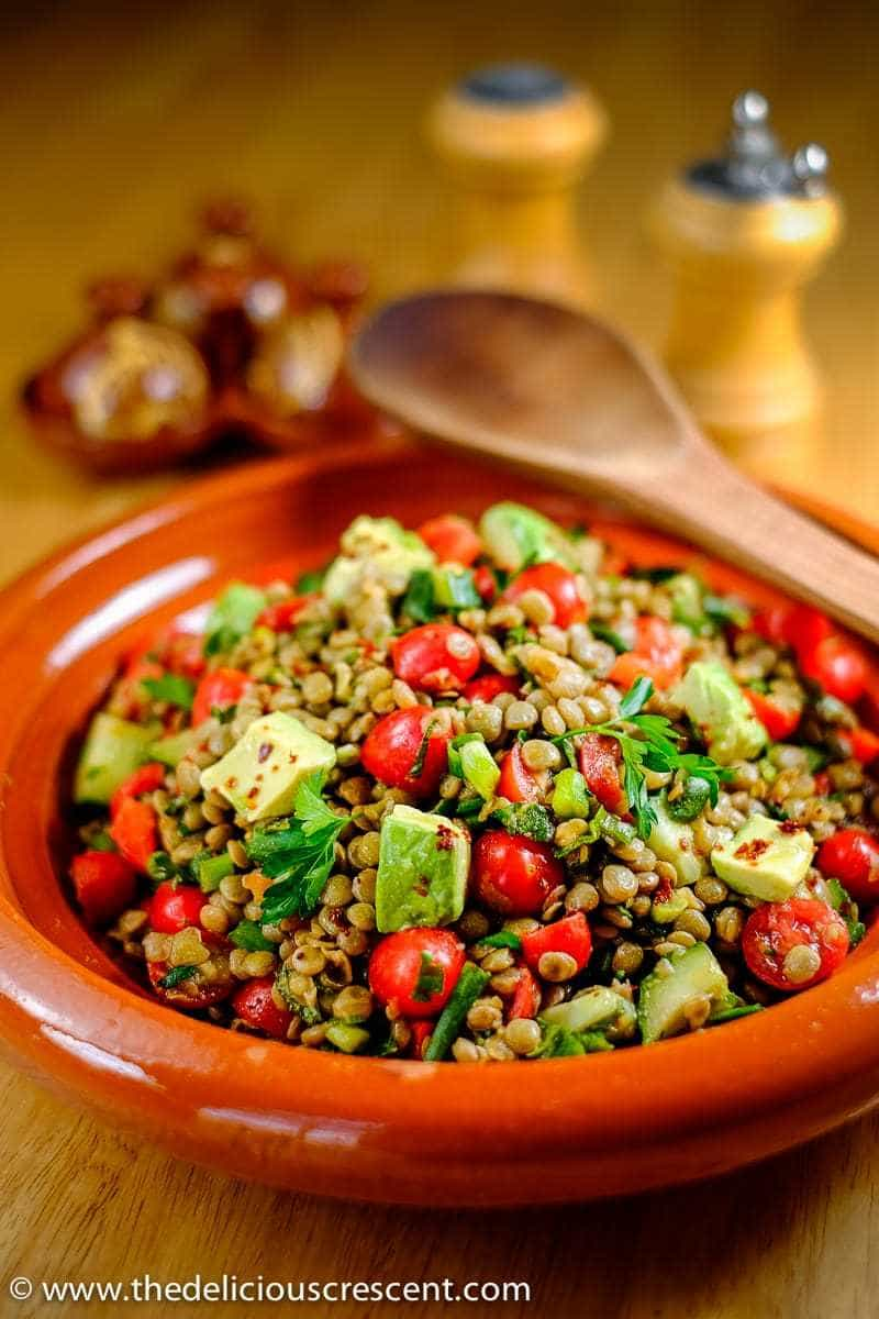 Spiced lentil salad with avocado served in a brown serving dish.