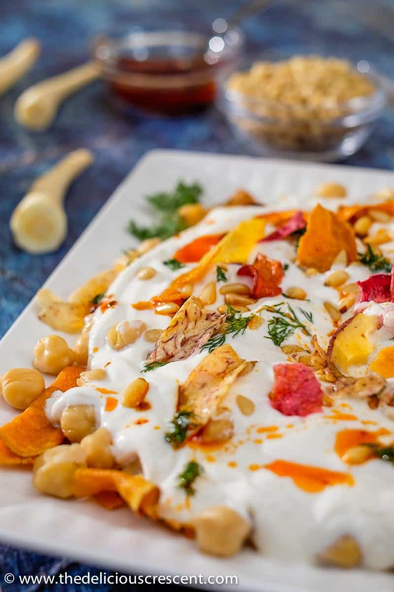 Chickpea salad with yogurt and vegetable chips served on a white plate.