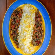 Almond herb crusted baked fish served with rice on a plate.