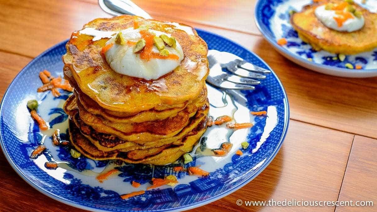 A stack of carrot pancakes served on a plate.