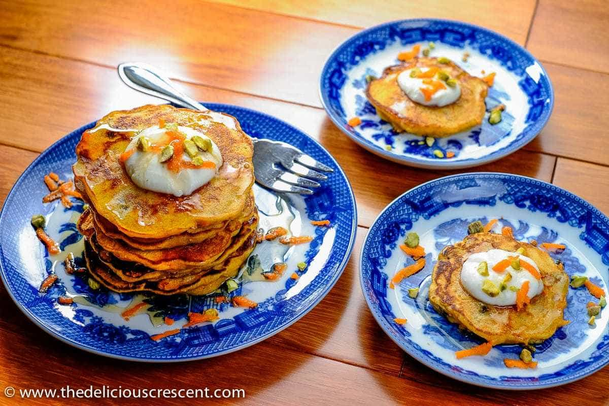 Dessert pancakes made with carrots served on three plates.