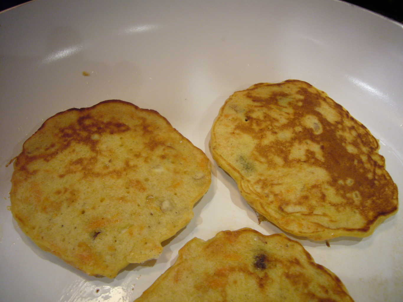 Three carrot pancakes flipped after cooking one side.