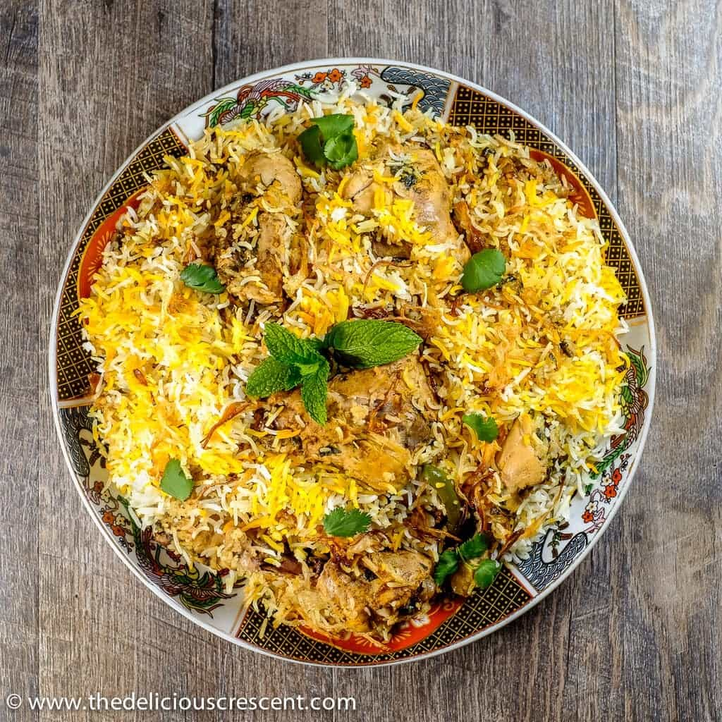 Easy Hyderabadi Chicken Biryani, famous authentic Indian delicacy with succulent chicken in layers of fluffy rice, fragrant spices and caramelized onions.