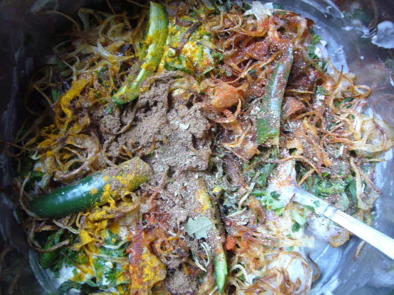 All the marinade ingredients, spices, herbs, chili peppers placed together for making the rice dish.
