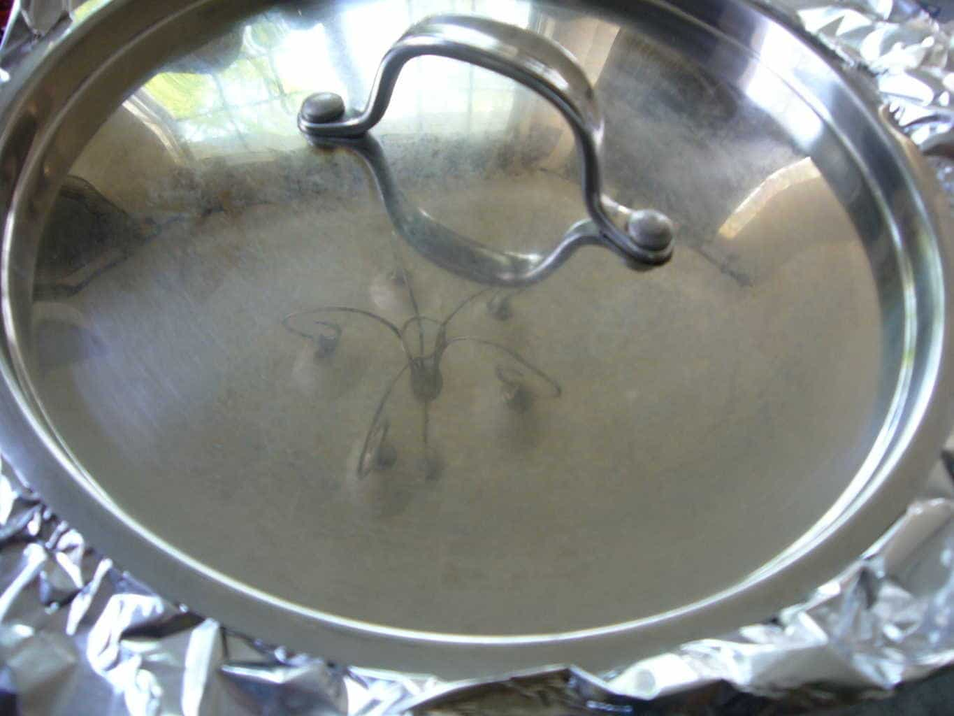 The lid placed over aluminum sheets and sealed tightly to steam the rice and chicken.