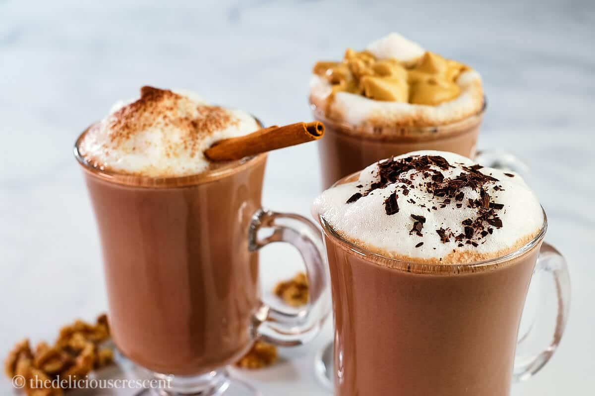 Steaming hot cocoa in glass mugs.