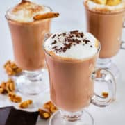 Creamy hot chocolate served in three glass mugs.