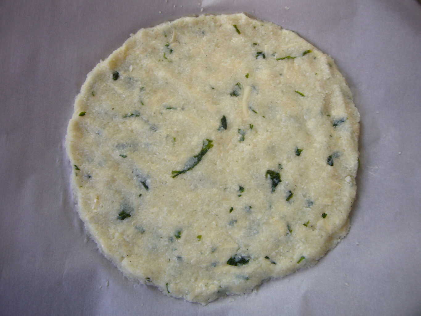 Cauliflower pizza crust mixture shaped for making a pizza.