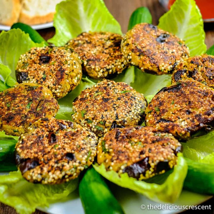 Chickpea patties with eggplant served over lettuce leaves in a plate.