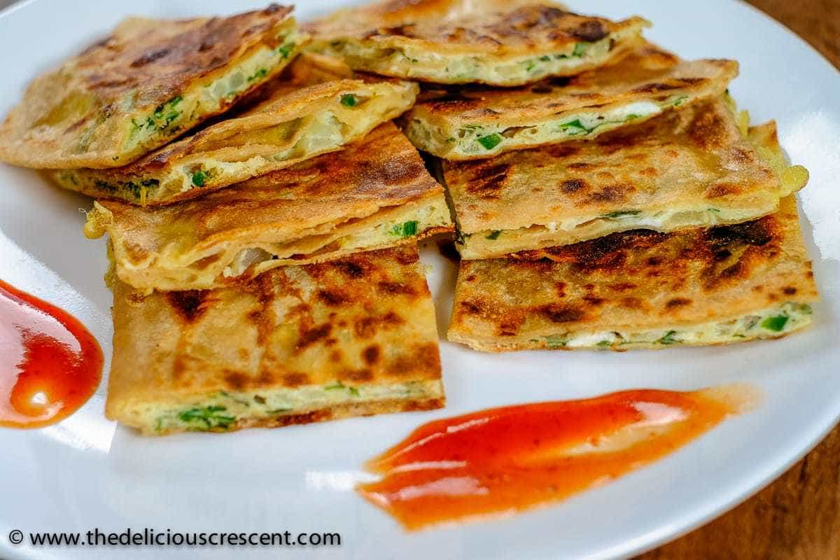 Egg paratha stuffed with omelette mixture, and cut into smaller pieces and served on a white plate.
