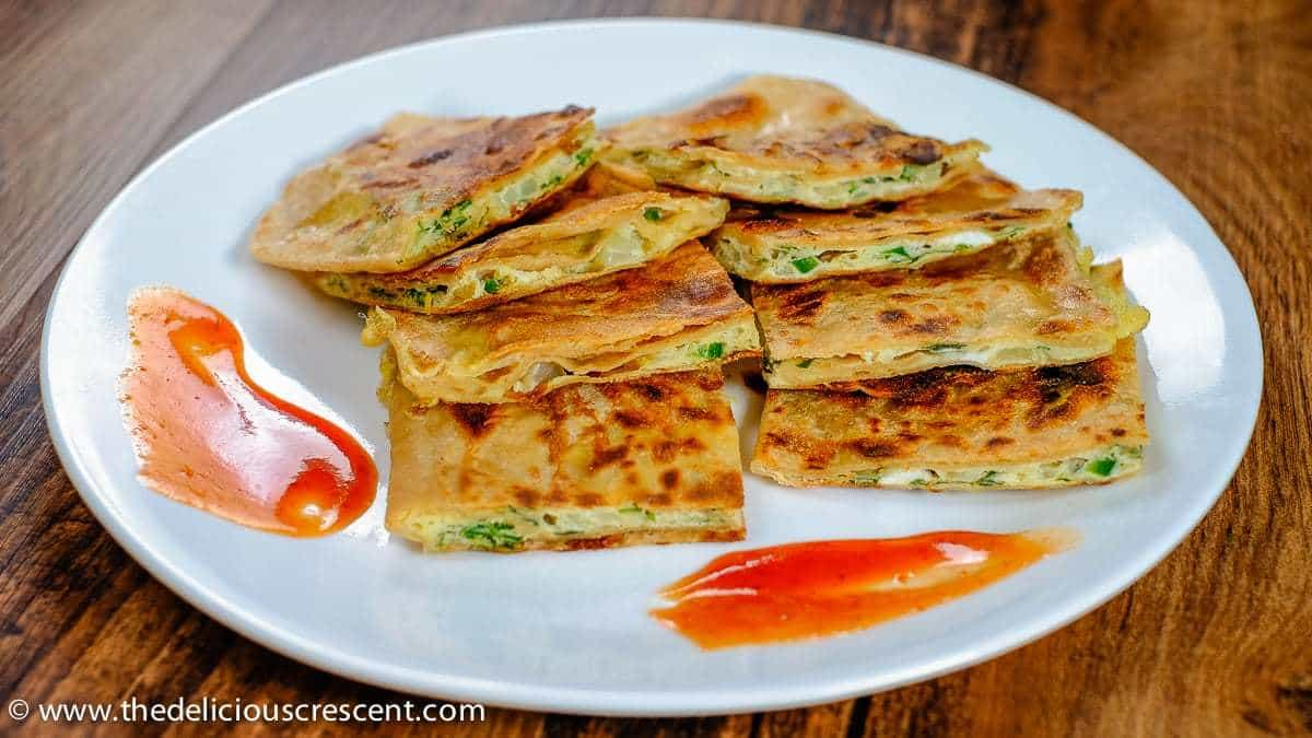 Front view of pieces of egg paratha served on a white plate.