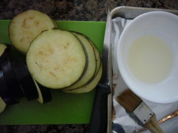 Eggplant slices to be brushed with olive oil before baking.