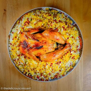 Zereshk polo ba morgh (barberry rice and saffron chicken) served on a plate.