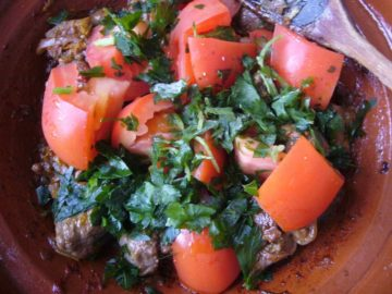 Tomatoes and herbs added to braised meat.