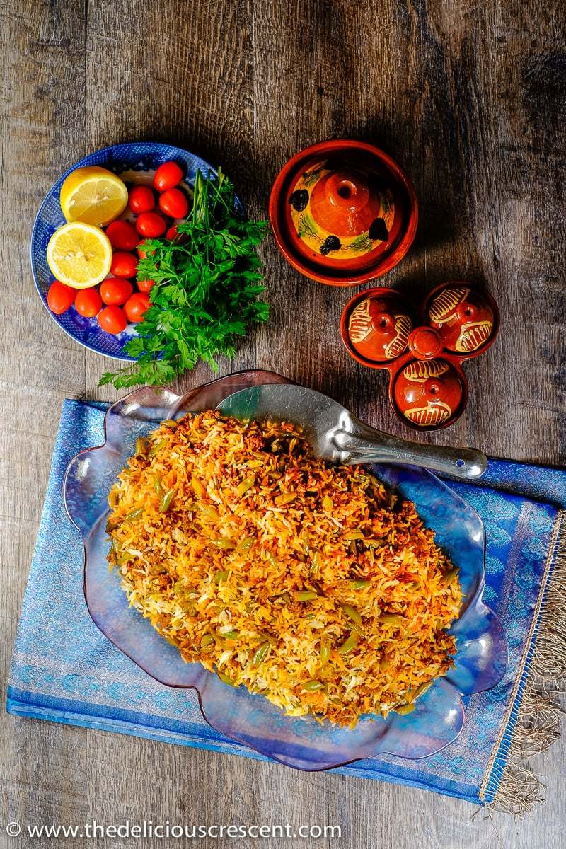Persian Lubia Polo (green bean rice) is a complete meal with an amazing taste, so quick and easy to prepare, with good protein, fiber and complex carbohydrates. It is a rice dish layered with green beans, spiced ground meat, tomatoes, herbs, lemon and infused with saffron.
