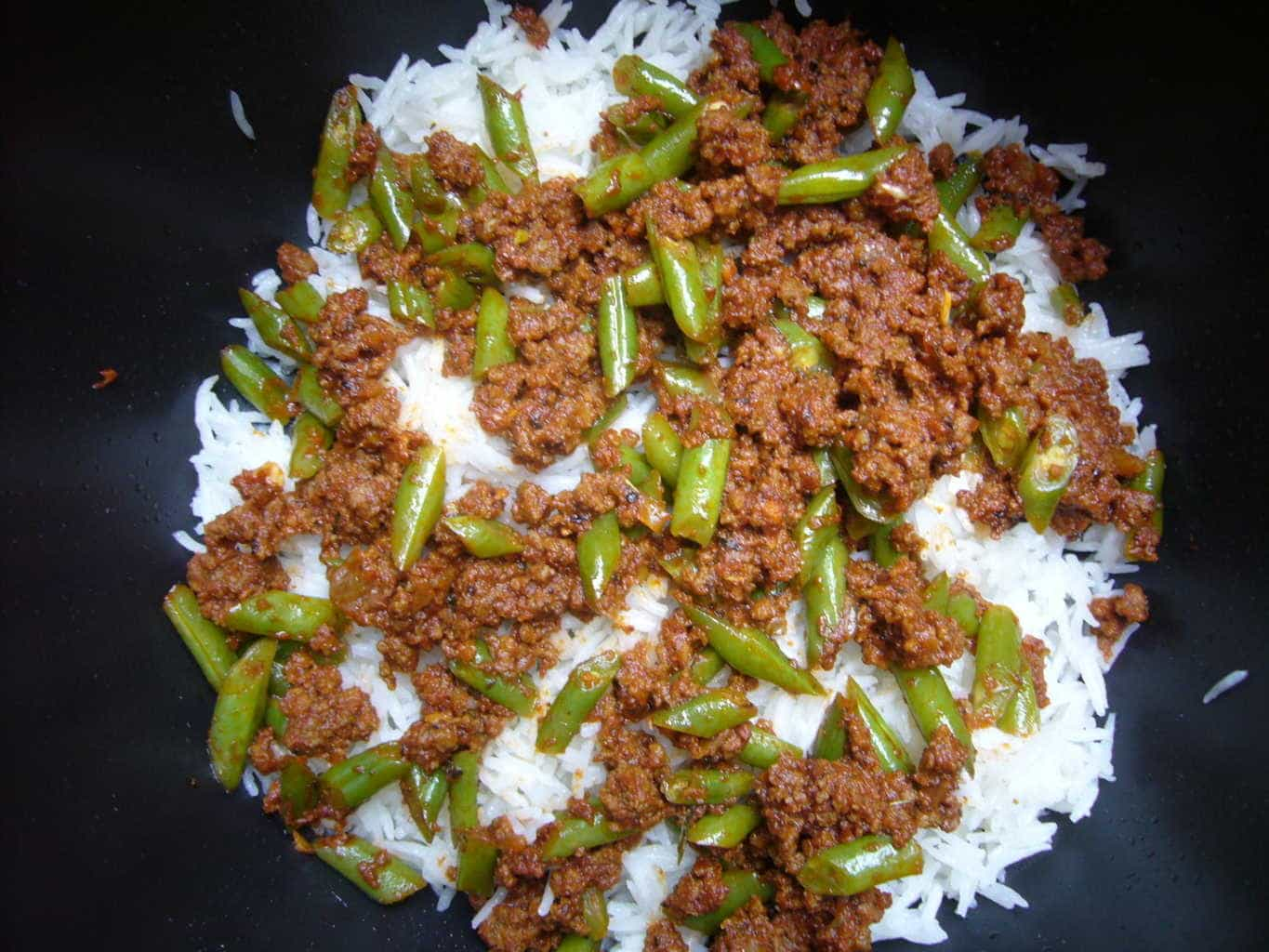 Meat and green bean mixture is layered with cooked rice to make lubia polo.