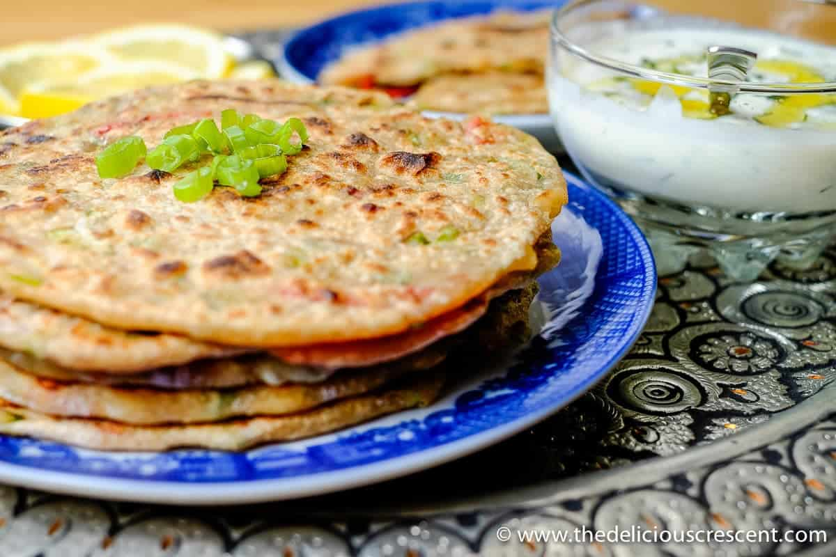 Stuffed Spring Onion Paratha is a whole grain, flavor packed, scrumptious Indian flatbread. Wholesome, with good amount of protein and fiber. Gouda Cheese, bell peppers (capsicum) and scallions come together in this wonderful and easy flatbread. Pair it with a Walnut Chutney or a Greek yogurt dip with grated garlic and dill for a splendid nutritious meal!