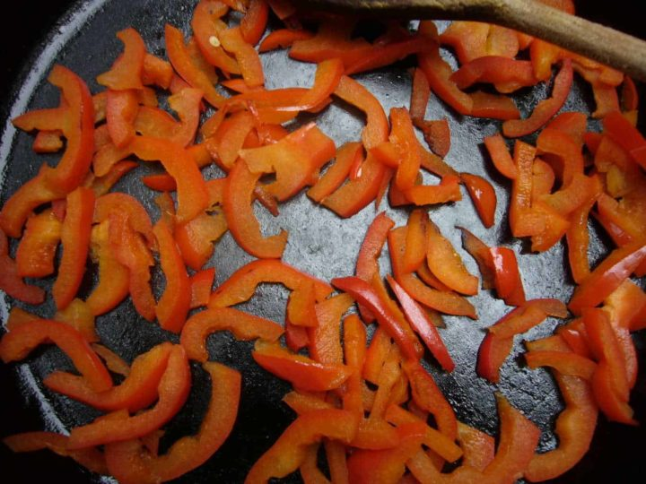 Red bell pepper sliced sauteed in a skillet.