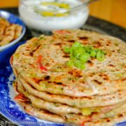 Cheese stuffed spring onion parathas stacked on a plate.