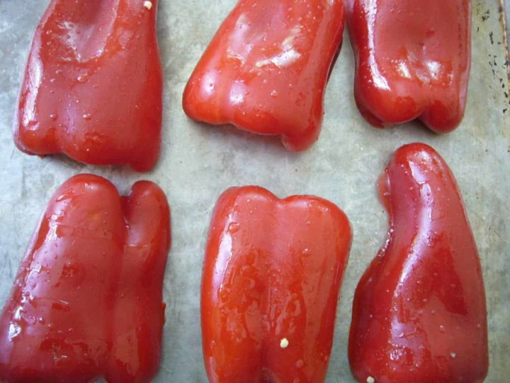 Red bell peppers placed on a baking sheet.