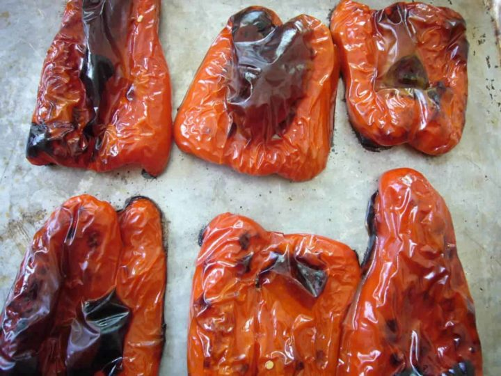 Roasted red bell peppers on a baking sheet.