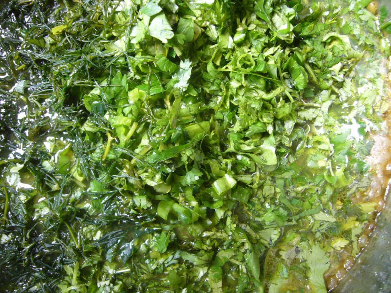 Fresh greens and herbs added to make Persian noodle soup.