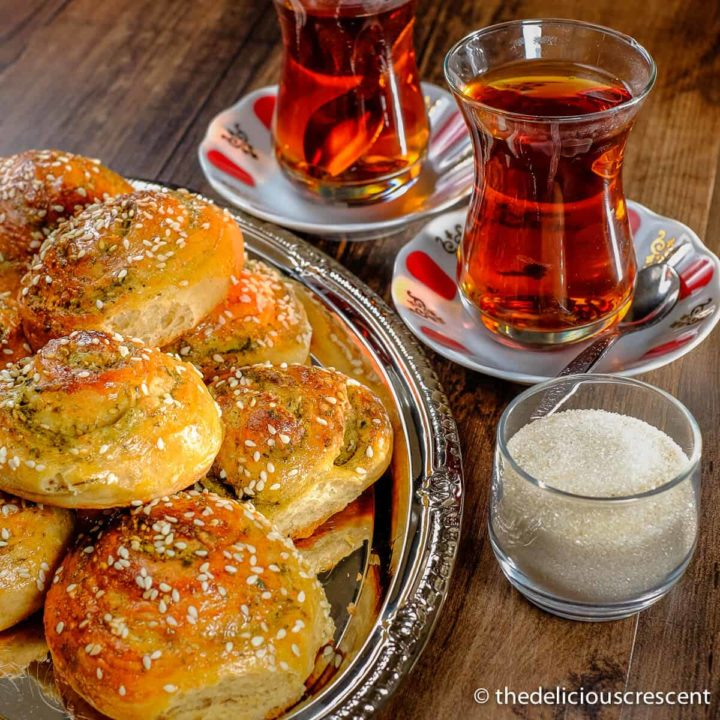 Zaatar bread rolls served on a plate along with tea.