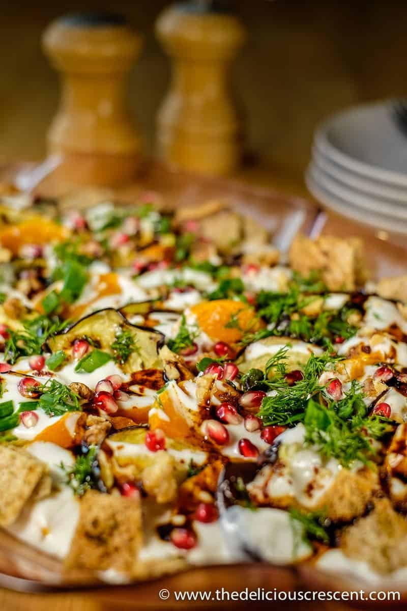 "Eggplant Yogurt Salad, an adapted version of the popular dish ""Fatteh"" with added butternut squash. It is so tasty with roasted vegetables in creamy yogurt sauce with crunchy pomegranate, walnuts and crispy pita chips."