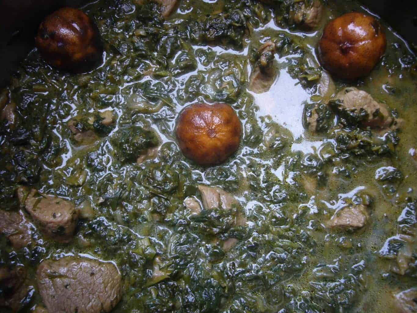Ghormeh sabzi with dried limes cooking in a pot.