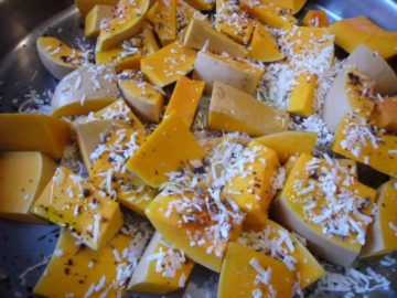 Butternut squash pieces topped with coconut flakes and spices.