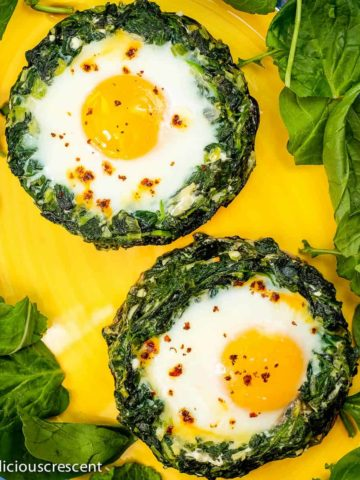 Portobello mushrooms stuffed with spinach, eggs and feta cheese, served on a plate.