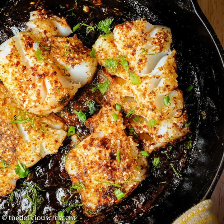 Pan seared fish with tamarind sauce served in a cast iron skillet.