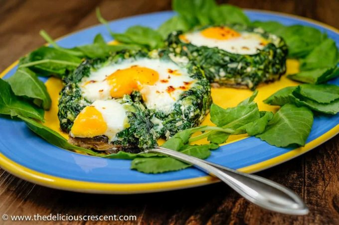 Two spinach egg stuffed mushrooms on a serving dish with a steel fork.
